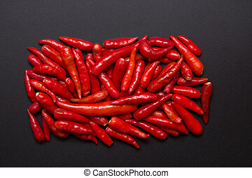 Heap of non-stem red bird eye chili pepper on grey...