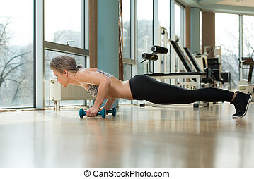 Young Woman Doing Press Ups In Healthy Club