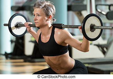 Barbell Squat - Beautiful Fit Woman Doing Barbell Squats In...