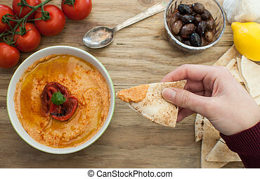 Dipping pita bread in hummus - Dipping pita bread in red...