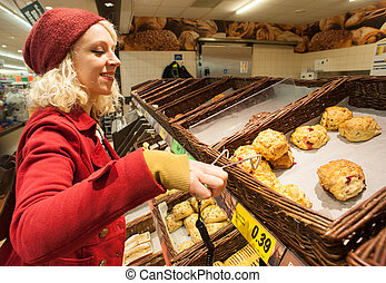 woman buying scones at bakery - Young woman buying scones at...