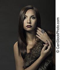 Woman beauty portrait in luxury fur coat. Beautiful girl on dark background.