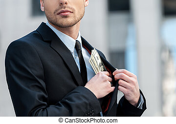 Pocketing company money Cropped shot of a businessman...