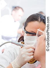 Working dentist - A young dentist treating an old womans...