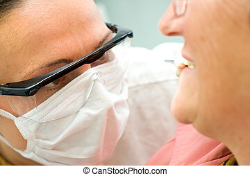 Examination at the dentist - A young dentist examining an...