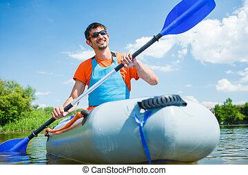 Man kayaking - Man paddling a kayak on the river, enjoying a...