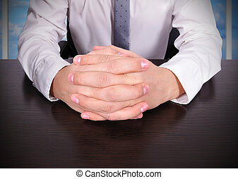 crossed fingers - businessman sitting with crossed fingers