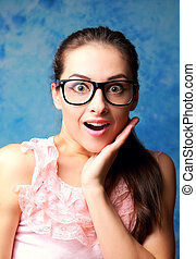 Surprising woman in glasses with opened mouth and hand at...