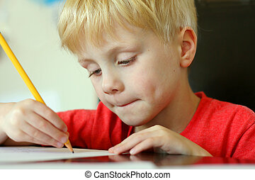 Young Child Drawing on Paper with Pencil - a young,...