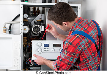 Technician servicing heating boiler - Technician servicing...