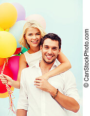 couple with colorful balloons at seaside - summer holidays,...