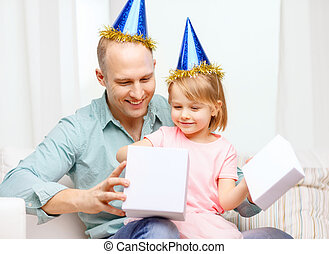 father and daughter in blue hats with gift box - family,...