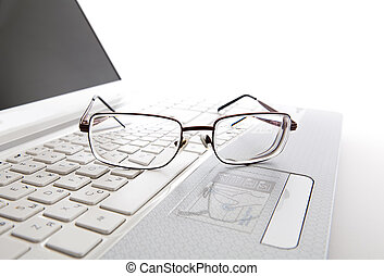 Eye glasses on a laptop keyboard on a white