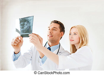 smiling male doctor or dentist looking at x-ray - medicine...