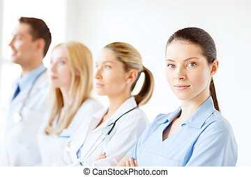 female doctor or nurse in front of medical group -...