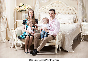 Young happy family with two baby boys at home