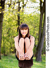 barefoot woman sitting on bench in park