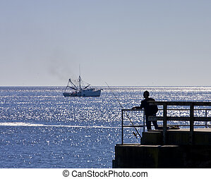 Fisherman and Shrimp Boat - A shrimp boat with a man fishing...