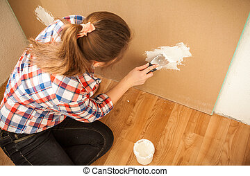 Woman plastering wall at house