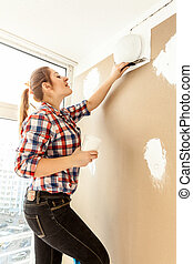 Female painter wall - Female painter plastering gypsum...