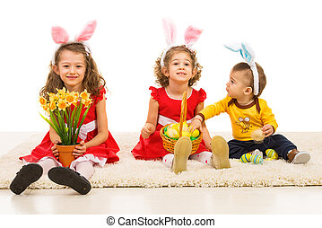 Happy three kids with bunny ears sitting in aline on carpet...