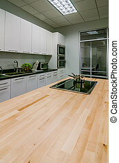 kitchen butcher table island with stove top and pans -...