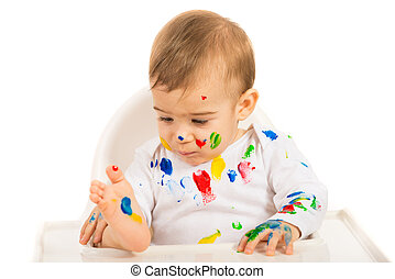 Baby boy looking at colorful paints on his body isolated on...