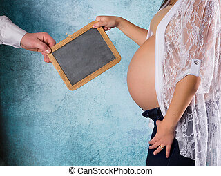 Pregnant parents holding empty board