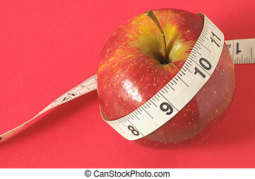 Diet Apple - Measuring Tape Wrapped Around Red Apple as a...