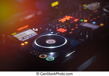 Disc Jockey mixing deck and turntables at night with...