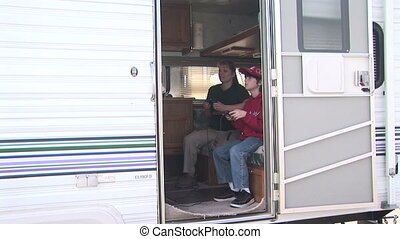 Two people playing video games inside an R.V. Trailer - A...