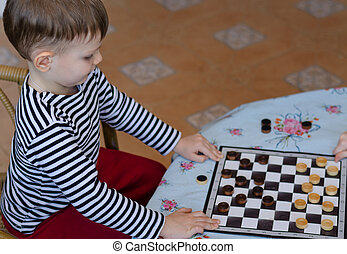 Little boy setting up a game of checkers or draughts on a...