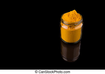 Powdered Tumeric Spices - Powdered tumeric spices over black...