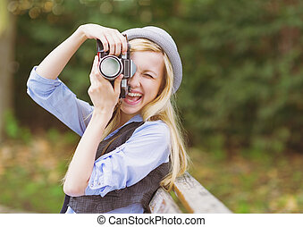 Young hipster taking photo with retro photo camera sitting...