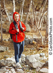 Happy smiling hiker boy with backpack in forest. Dressed in...