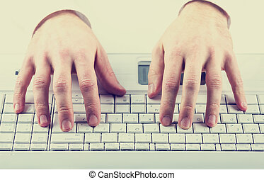 Man typing on a computer keyboard - Toned instagram effect...