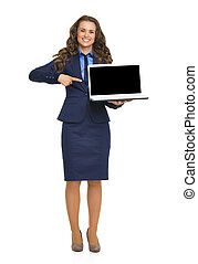 Full length portrait of happy business woman pointing on...