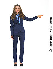 Full length portrait of smiling business woman pointing on...