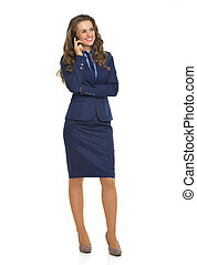 Full length portrait of happy business woman talking cell phone