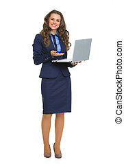Full length portrait of happy business woman with laptop