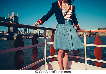 Young woman on the deck of ship with skirt blowing in the...