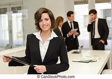 Business leader looking at camera in working environment -...