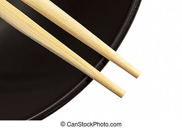Chopsticks on a black bowl with white background
