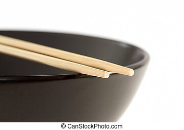 Two chopsticks on a black bowl with a white background