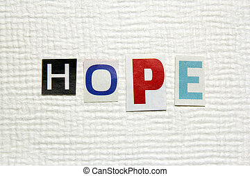 hope word cut from newspaper on handmade paper background