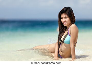 Beautiful young Filipina woman at the seaside sitting in the...