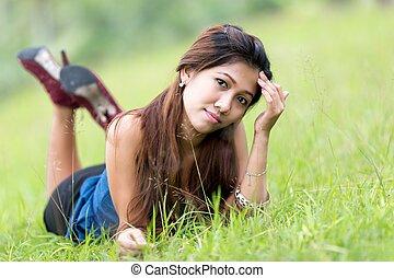 Beautiful young Filipina woman enjoying nature lying on her...