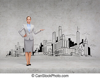 smiling young businesswoman showing town sketch - business...