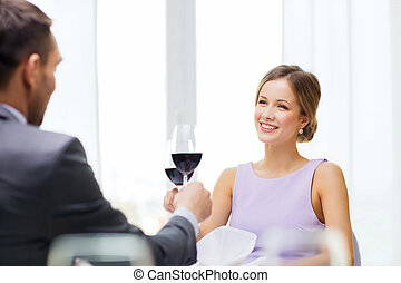 young woman looking at boyfriend or husband - restaurant,...