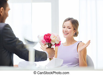 amazed woman recieving bouquet of flowers - restaurant,...